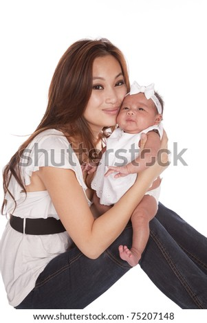 a oriental mother holding her beautiful daughter on her knee.