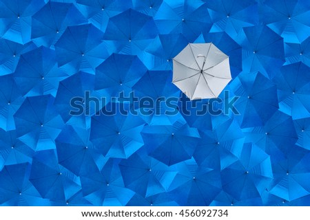 A overturn grey umbrella is different from the blue umbrellas, Being different concepts, Business concept, The failure or the error, The bankrupt, One person who fails, See from top view.