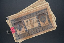 A pack of old tsarist Russian rubles and a modern paper clip