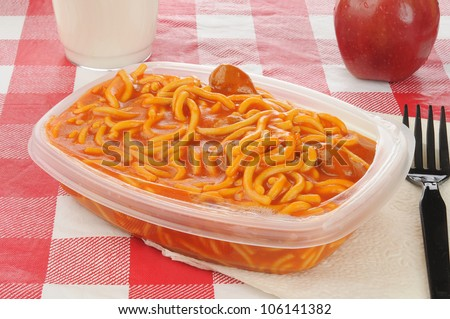 A packed lunch with microwave spaghetti an apple and milk