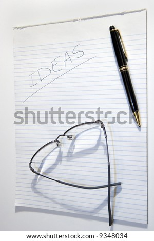 A pad of paper for Ideas with a pen and glasses