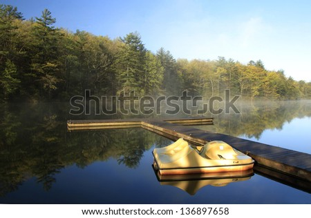 A paddle boat at dock reflected in a beautiful mountain lake at sunrise