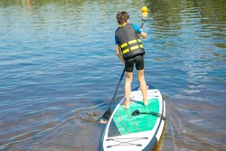 A paddler-boarder. Photo of 10-year-old Boy rowing on a standing Board. Healthy lifestyle. Water sports, SUP surfing tour in an adventure camp on active summer beach holiday. Healthy active lifestyle