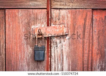 A padlock on a rustic wooden barn door