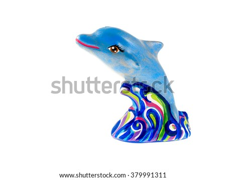 A painted clay figurine of a dolphin jumping out of the sea waves