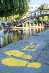 A painted sign on the floor asking people to social distance next to the canal with a bridge in the background at Camden Market