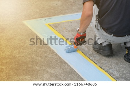 A painter painting parking lots blue lines striping in a car park. #1166748685