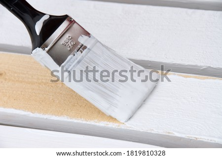 A painter primes the wooden slats of a fence that is being constructed. Stockfoto ©
