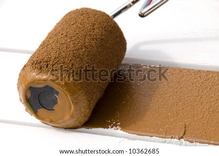A painter rolls brown paint on freshly primed wood