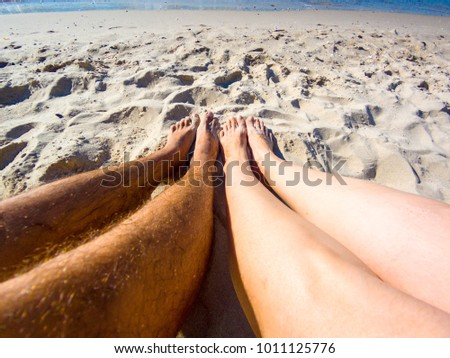 A pair hairy of male and female bare legs lie on the sand of the beach