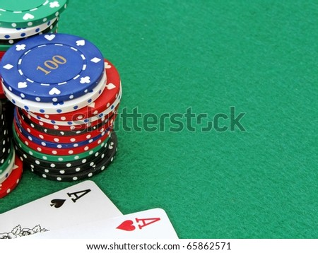A pair of aces next to a stack of poker chips on a green felt background with copy space