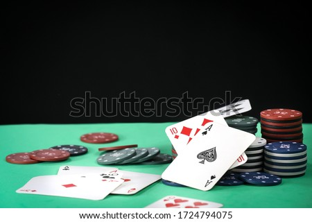 A pair of aces on a deck of playing cards. Poker playing chips on a green table. Online gambling. Addiction. Playing cards and poker chips. Copy space.