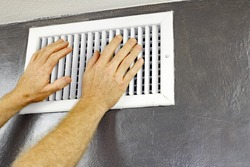 A pair of adult male hands feeling the flow of air coming out of an air vent on a wall near a ceiling. Man with hands in front of an air vent feeling for air flow.