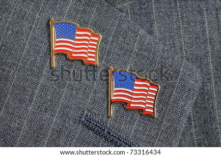 A pair of American flag pins on a pinstripe suit lapel