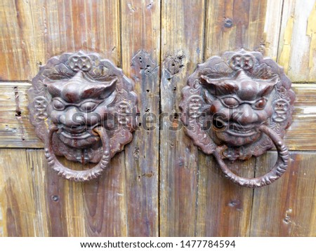 A pair of ancient metal Mythical Animals head gate holders on a wooden door on the street lane of Tianzifang in Shanghai city China.