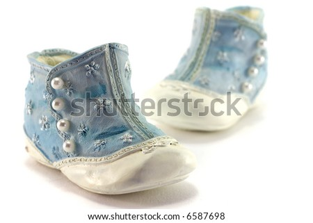 A pair of antique porcelain shoes on white background. - stock photo