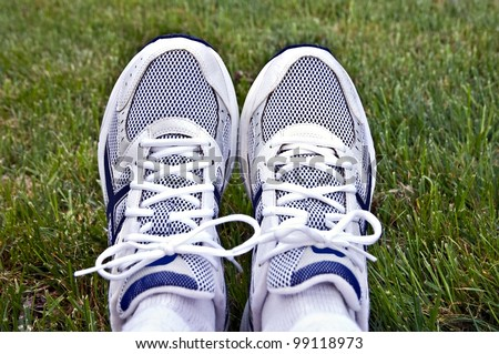 A pair of athletic shoes on a background of grass.