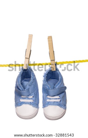 A pair of baby shoes hanging on a clothesline isolated on a white background.  Image was shot on a lighted white backdrop and is not a cutout.