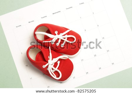 A pair of baby shoes on a monthly calendar to represent many parenting concepts.