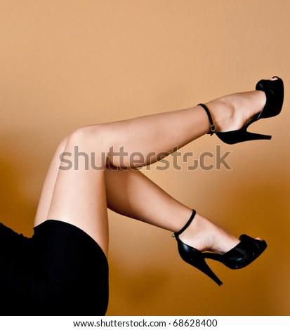 A pair of beautiful female legs on a orange background