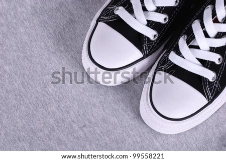 A pair of black canvas sneakers on grey textile background with copyspace