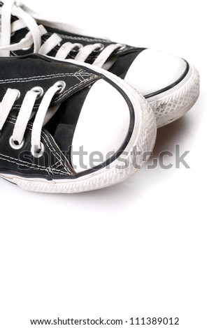 A pair of black canvas sneakers on white