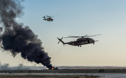 A pair of black hawk helicopters fly by and fire explosive rounds at distant targets in Tel Aviv, Israel.