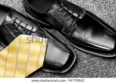 A pair of black leather dress shoes with a yellow necktie