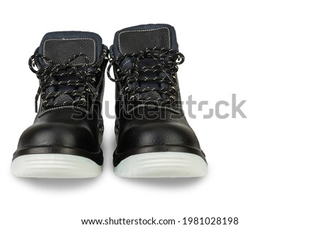 A pair of black leather work boots with thick gray soles on a white background. Front view. The shoes are new. The laces are tied. The image is isolated. The boots are on the left and have a shadow. C Stok fotoğraf ©
