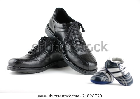 A pair of black man's shoes and a pair of blue baby shoes for the newborn. Father and son concept.