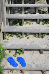 A pair of blue flip flops sit in the sand at the bottom of a set of beach access stairs.