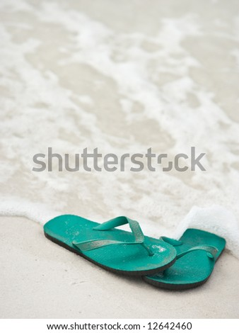 A pair of blue-green flip flops (thong sandals) at the water's edge at the beach. Good background shot.