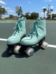 A pair of blue roller skates on a basketball court.