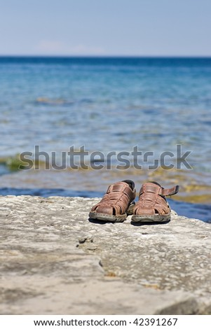 A pair of brown sandals on a rocky ledge, with an expanse of blue water and sky behind. - stock photo