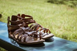 A pair of brown sandals sitting on a park bench outside- A pair of girl's brown sandals set on a bench- a pair of brown summer shoes- brown leather sandals