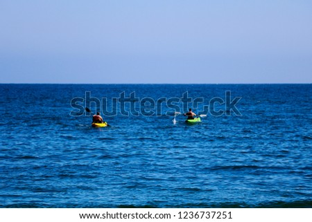 A pair of canoes in the Pacific. People kayak in the ocean.