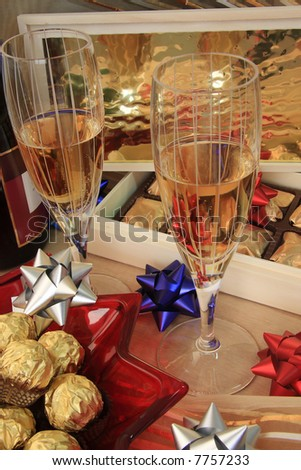 A pair of champagne glasses with chocolate candies