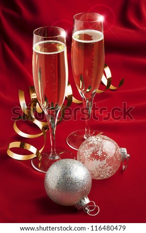 a pair of champagne glasses with christmas decorations