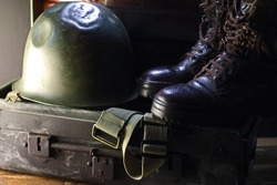 A PAIR OF COMBAT BOOTS ON A METAL TRUNK WITH A COMBAT HELMET AND CANVAS STRAPS