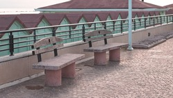 A pair of concrete benches on the sidewalk in front of beach cabins on the Mediterranean coast (Pesaro, Italy, Europe)