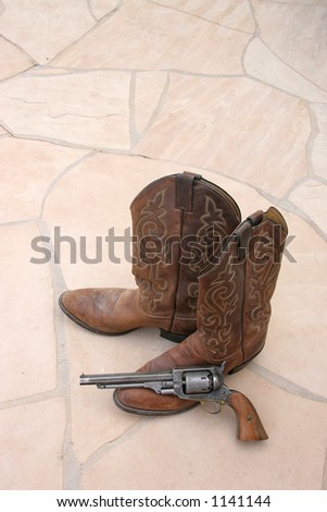 A pair of cowboy boots and a revolver on flagstone.