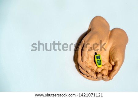 A pair of cupped hands hold and care for technology that everyone seems to enjoy most, their phones / smart phones.