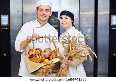 a pair of cute young bakers-a guy and a girl in white chef's tunics holding a basket with a large assortment of pastries and a bouquet of dry wheat ears against the background of the bread production  Foto d'archivio ©