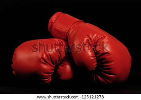 A pair of dark red vintage boxing gloves on black background