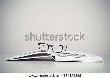 A pair of designer glasses on an opened coffee table book.