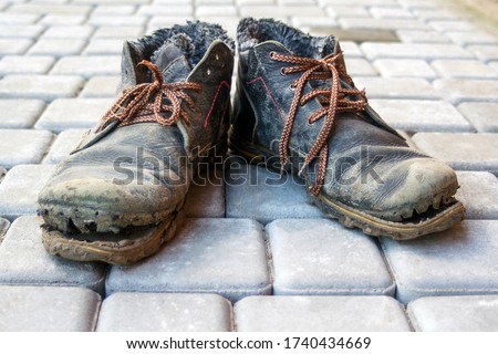 A pair of dirty boots. Old worn dark blue leather shoes with variegated brown laces. Background from gray pavers. The concept of poverty, homelessness, lack of money. Selective focus Stock photo ©