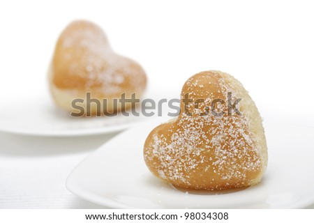 a pair of donuts heart-shaped on saucer, on white background
