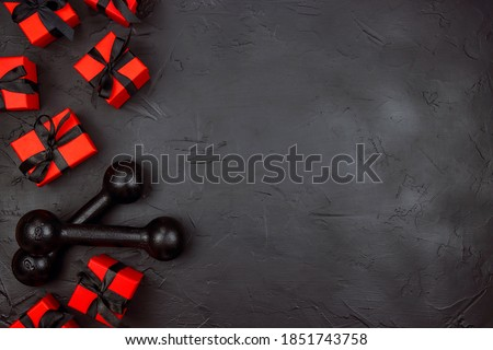 A pair of dumbbells and red gifts with black ribbons on a black background.  Holiday fitness sale or black friday concept. Top view with copy space.