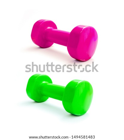 A pair of dumbbells green and glamours pink, isolated on white background. Fitness equipment, healthy lifestyle concept.
