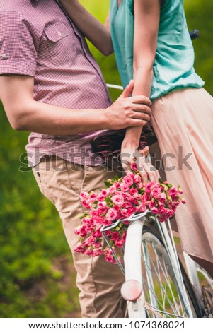 a pair of enamored stand near a bicycle with an inscription and a basket of flowers in the summer in the park #1074368024